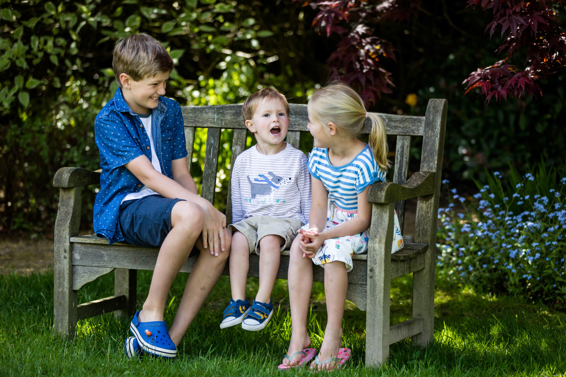 three siblings sitting on a bench chatting to each other