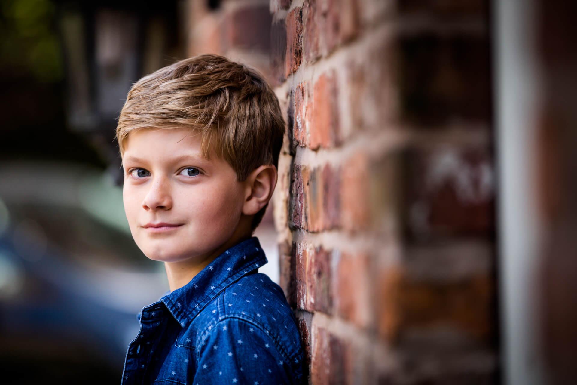 portrait of a teenage boy leaning against a wall