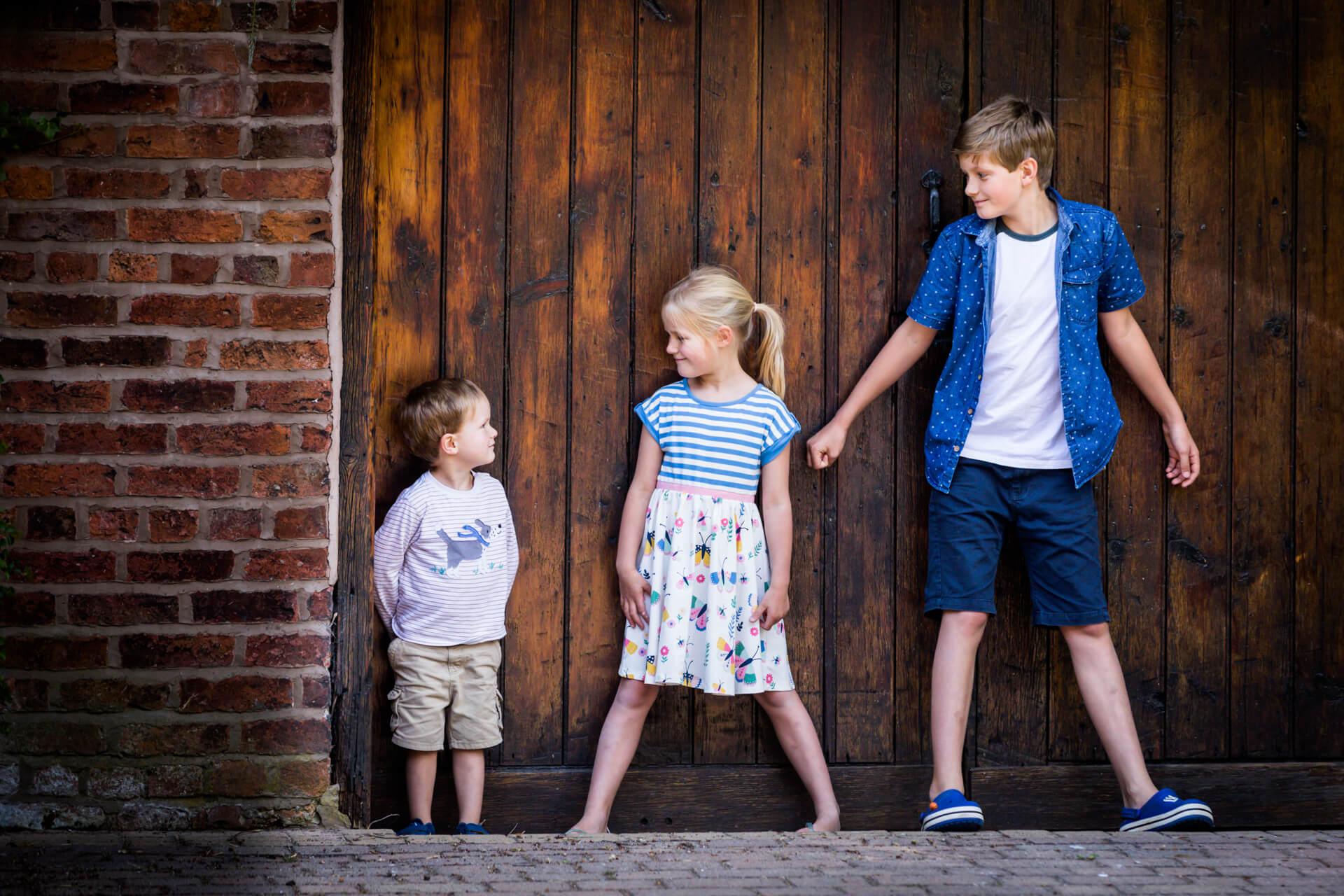 siblings standing together in front of a garage door