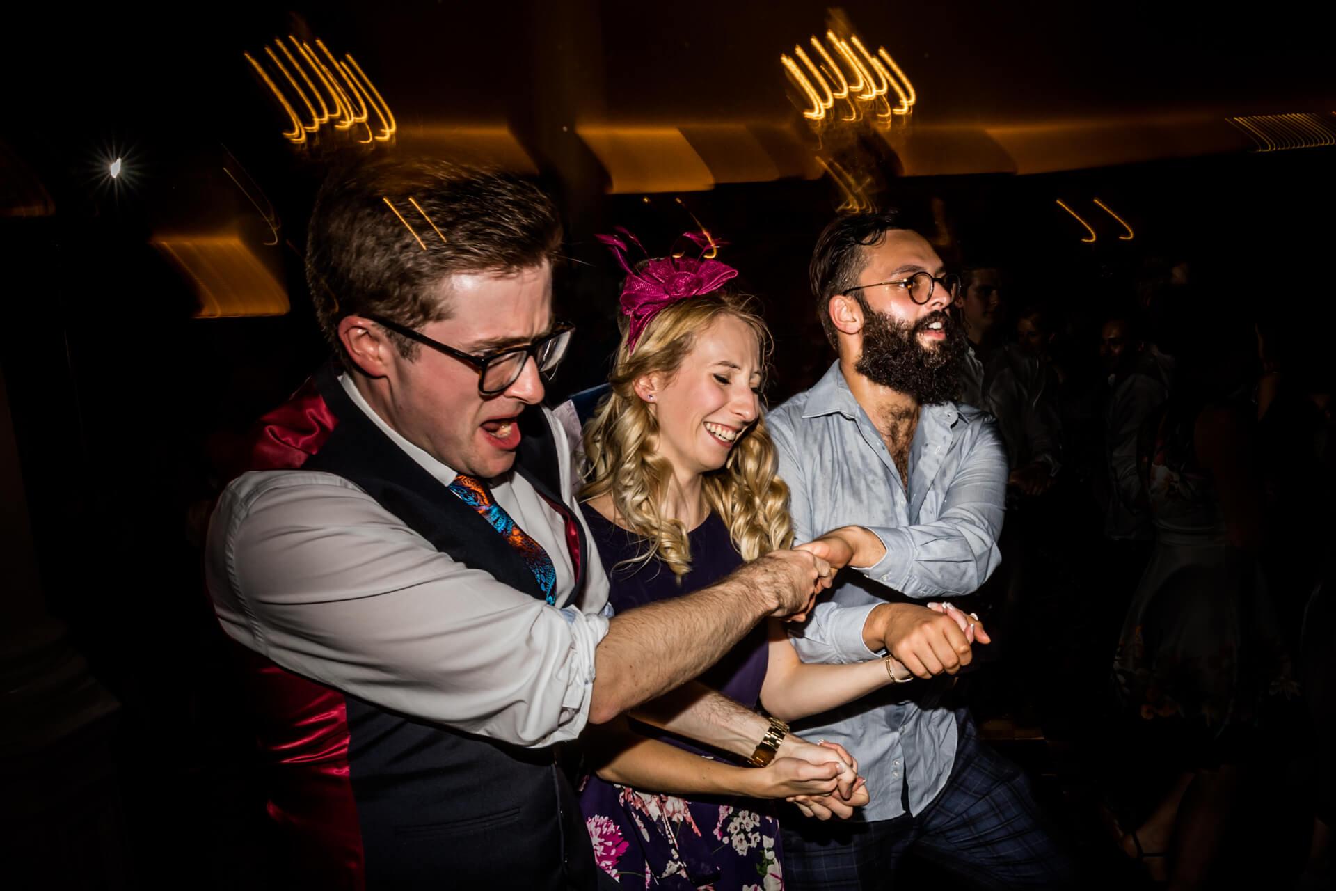 three wedding guests dancing arm in arm