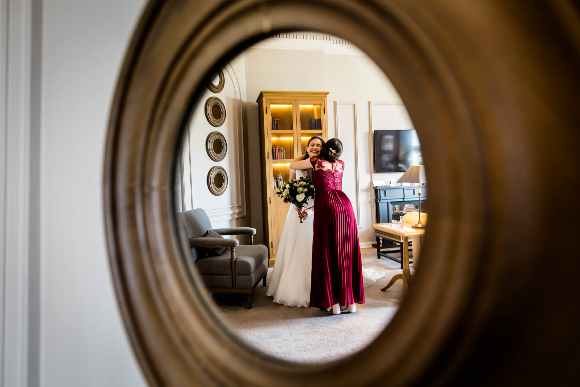 reflection in a mirror showing a bridesmaid hugging the bride