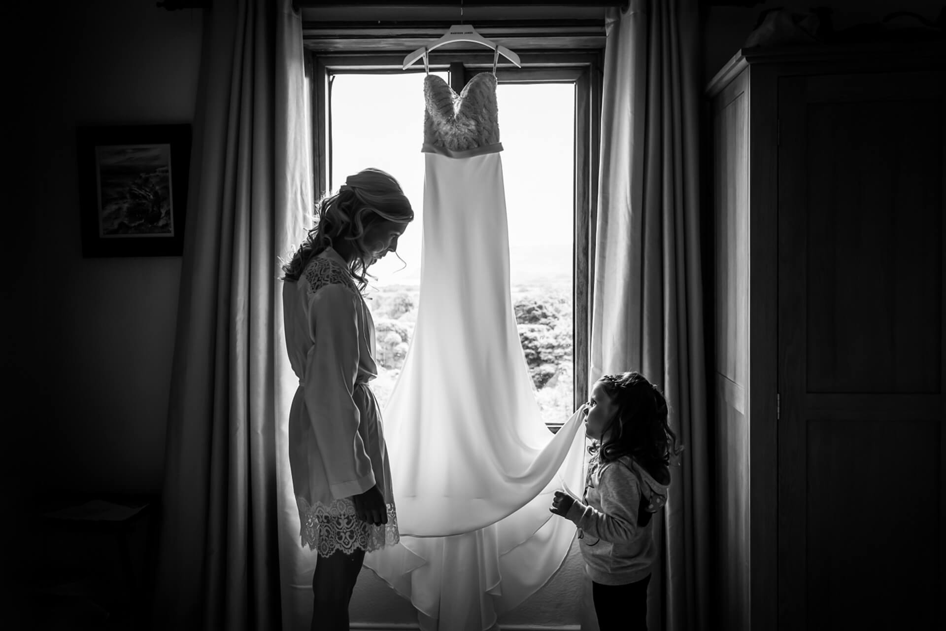 flower girl talking to the bride about her dress