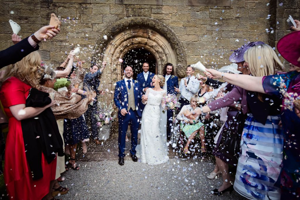Lake District Wedding Photographer - couple showered by confetti