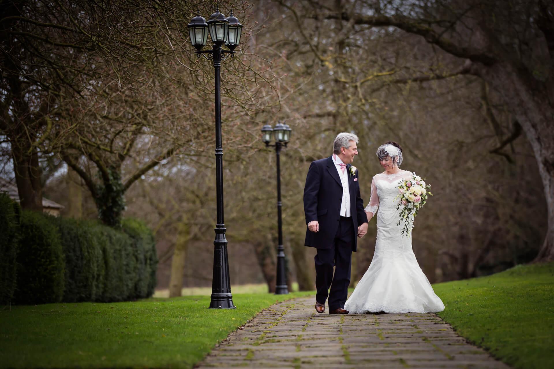 Hazlewood Castle wedding photographer - bride and groom walking in the castle grounds