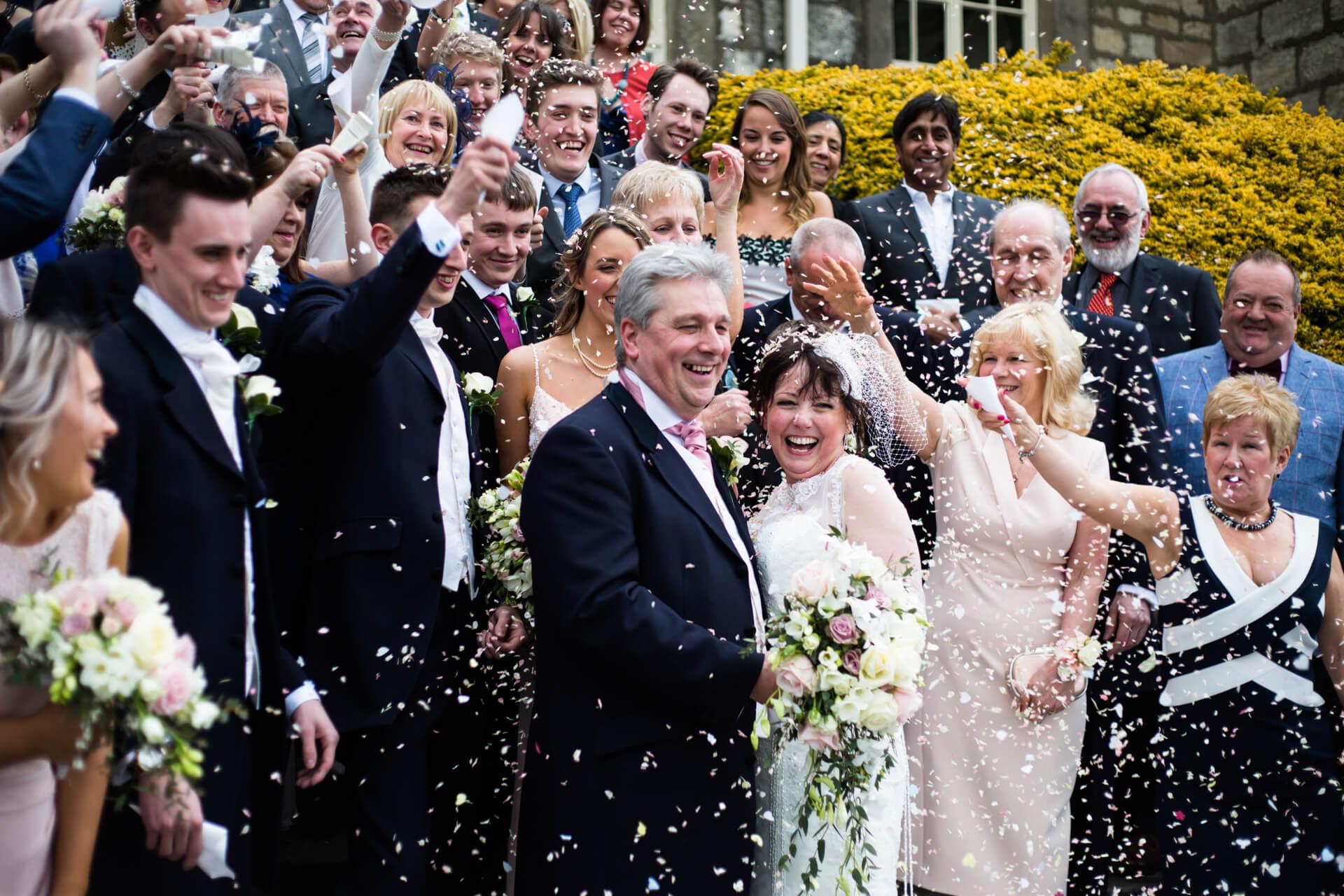 Hazlewood Castle wedding photographer - wedding couple under the confetti