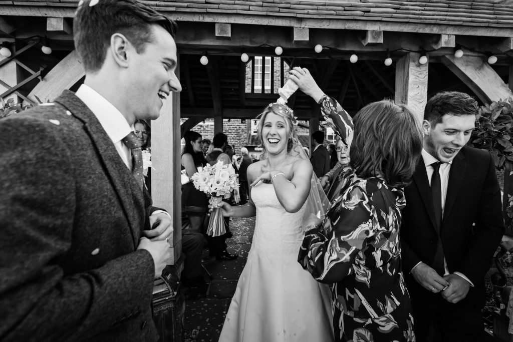 Hornington Manor Wedding Photography - guest tipping confetti over the bride