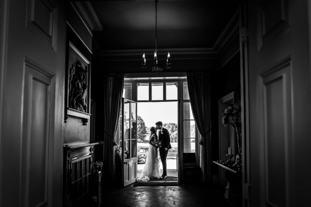 Silhouette of the bride and groom kissing in the doorway to Saltmarshe Hall