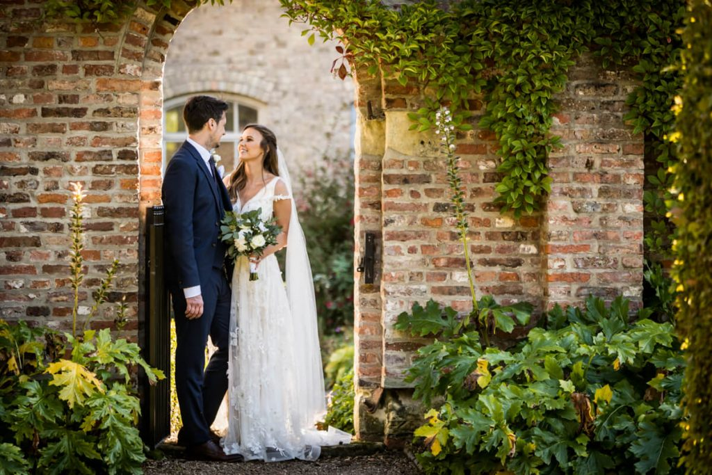 Saltmarshe Hall - bride and groom standing under a garden arch