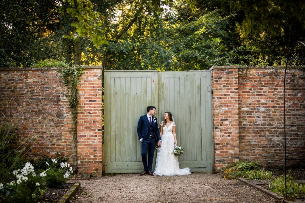 wedding couple leaning against a fence at Saltmarshe Hall