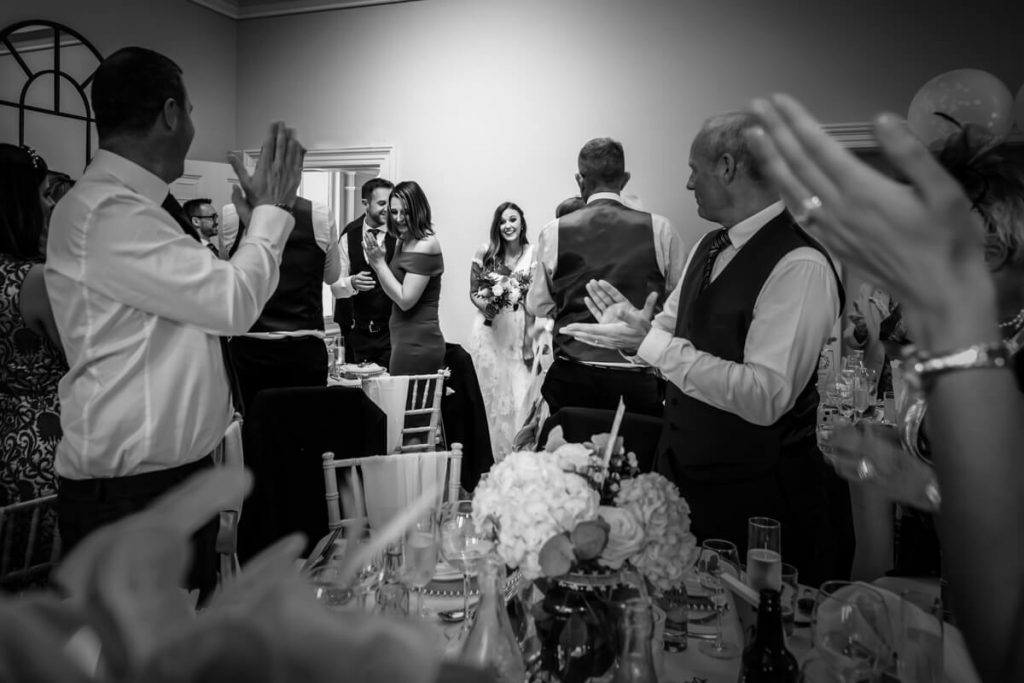 guests clapping as the wedding couple enter the room