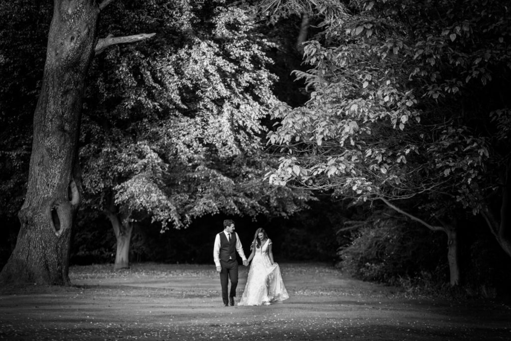 couple walking through the gardens at Saltmarshe Hall