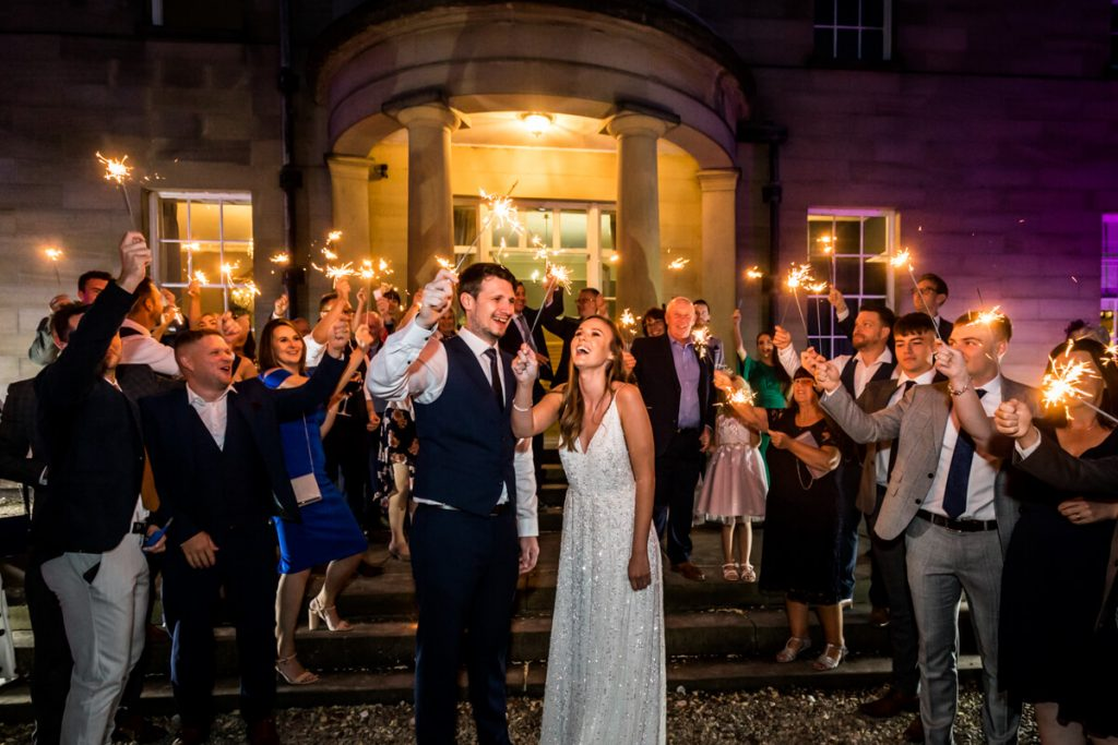 wedding couple and their guests waving sparklers outside Saltmarshe Hall