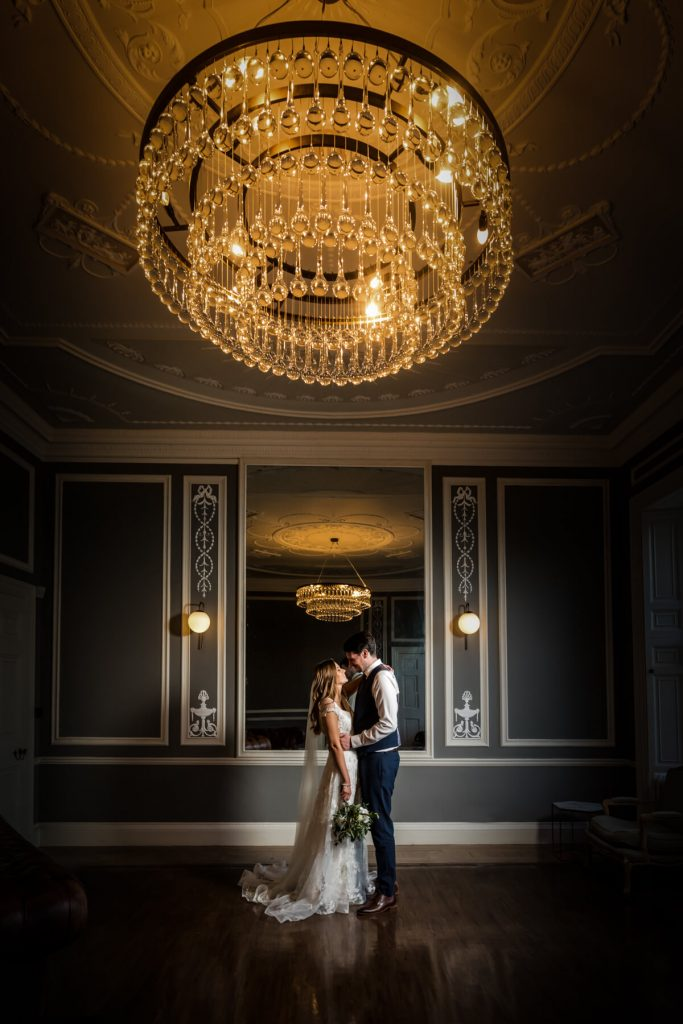 Saltmarshe Hall- wedding couple embrace under a stunning chandelier