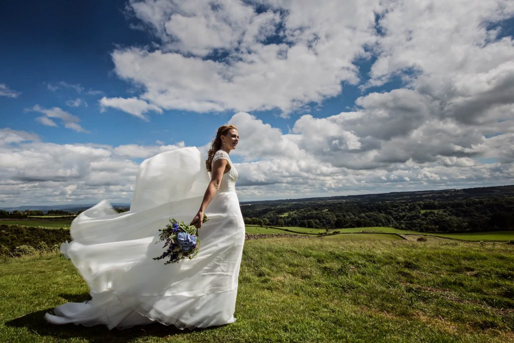 Bride in front of a Yorkshire dales view with her dress blowing