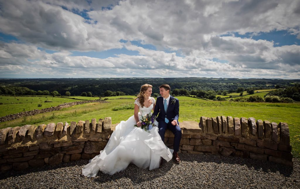 Wedding couple sitting on a wall in front of a Yorkshire Dales view