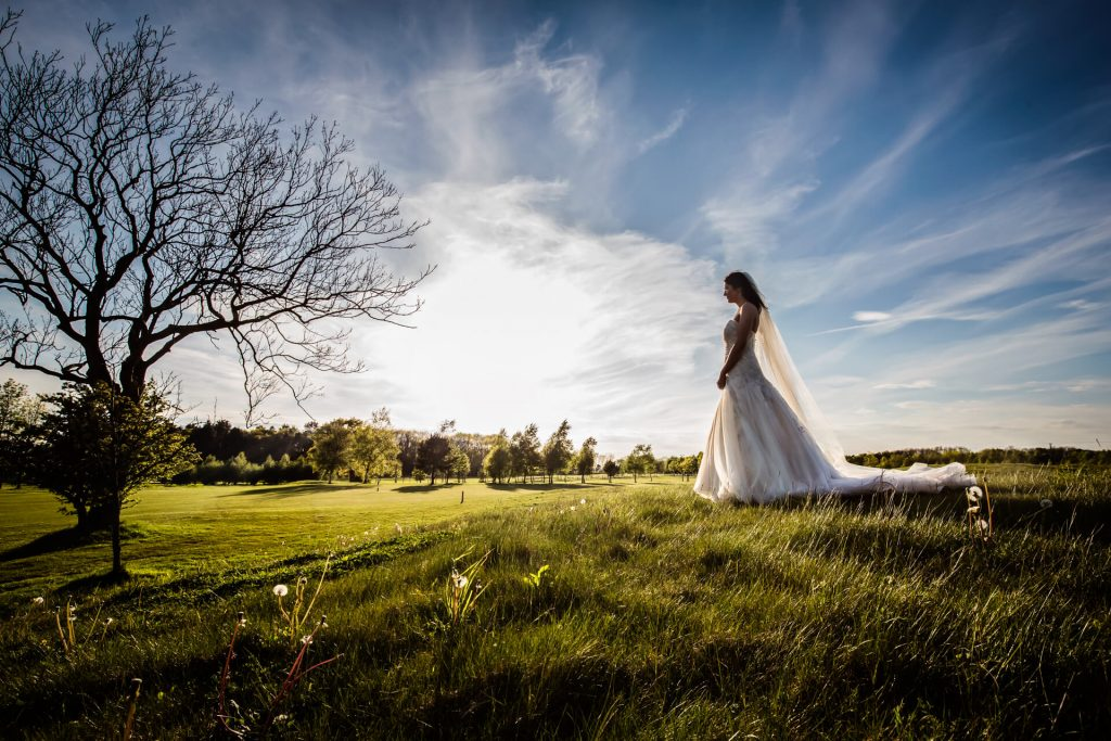 bride on a hill looking into the sun