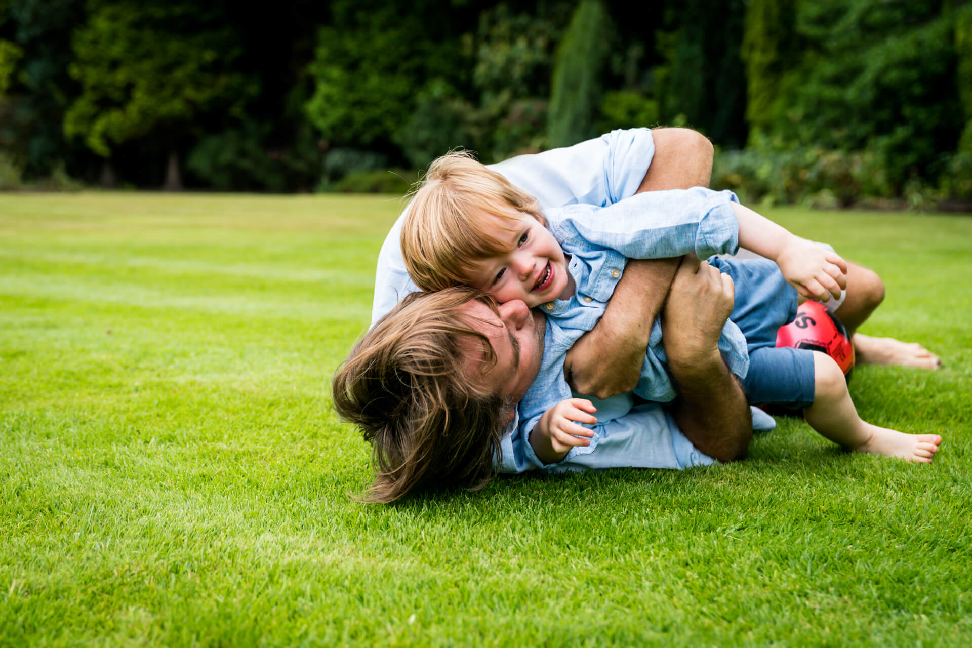 dad rolling on the grass with his son and laughing