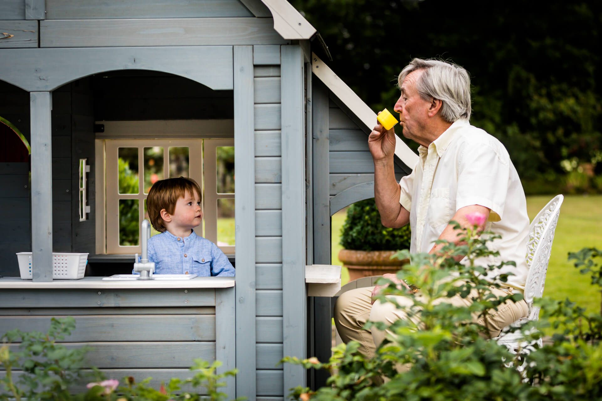 small boy in his play house offering a cup of tea to his grandad