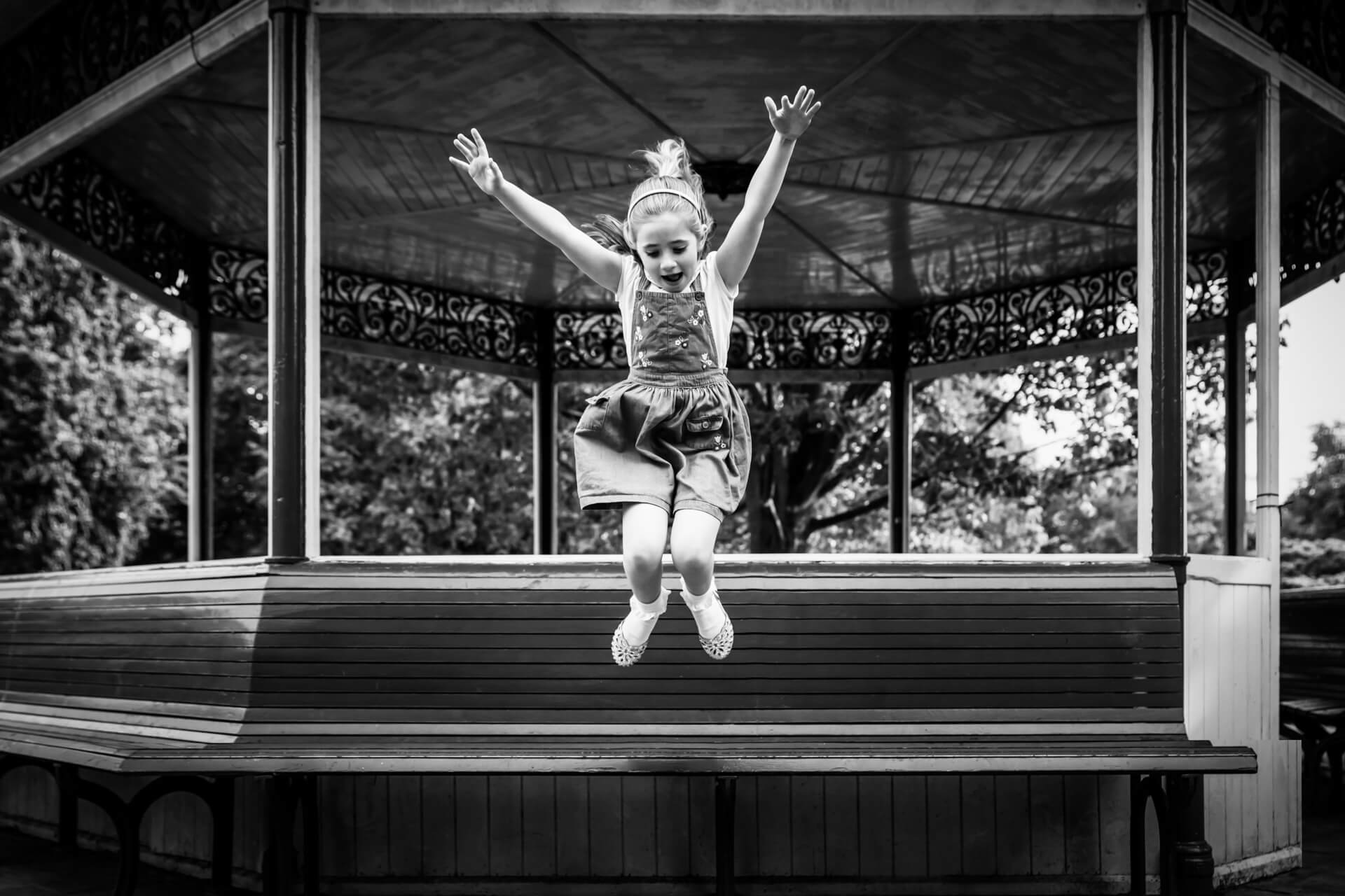 girl leaping off a park bench