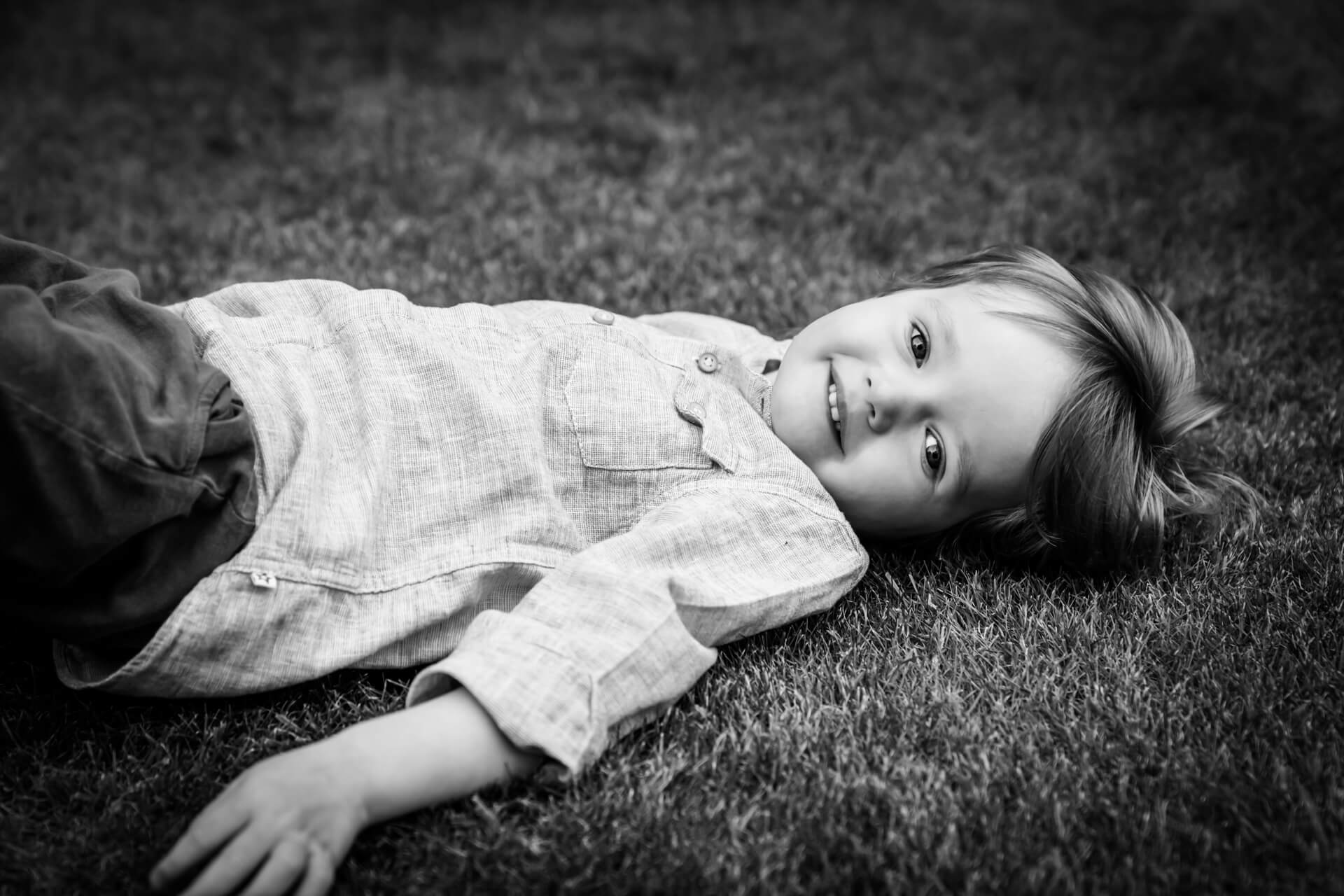 small boy lying on the grass
