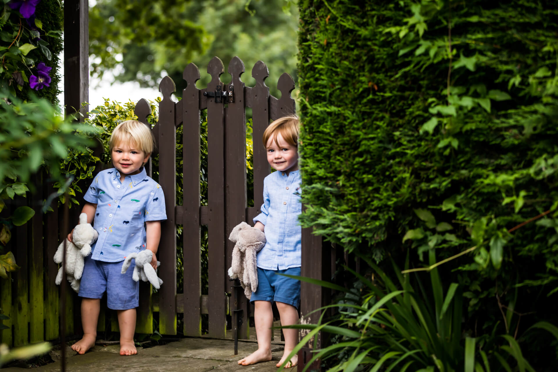 two boys standing by a garden gate holding teddy bears