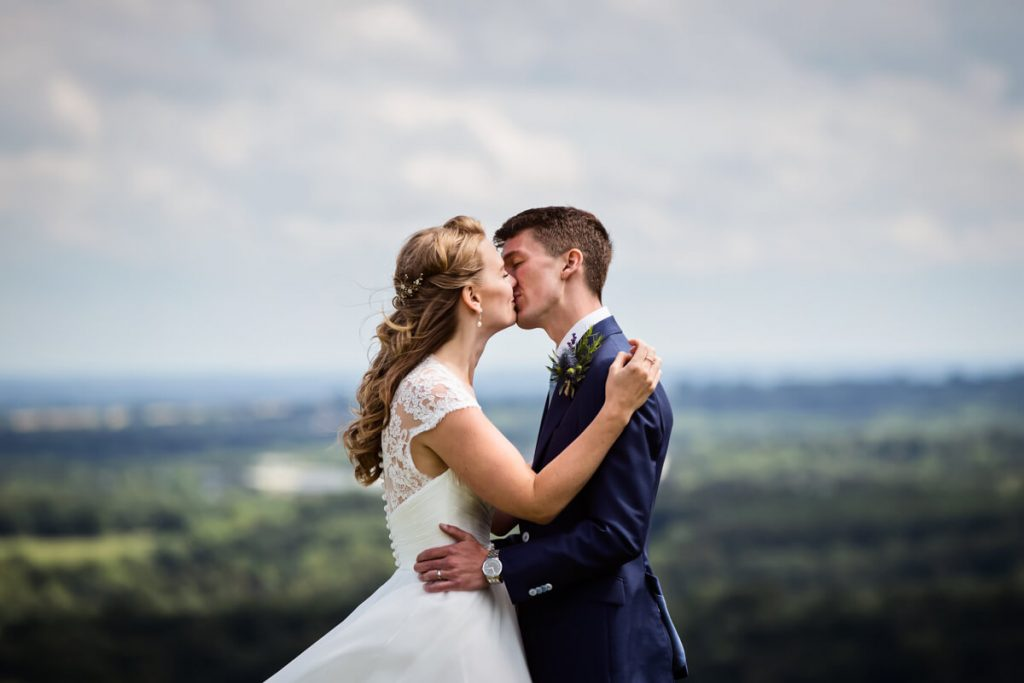 bride and groom kissing in front of a yorkshire view