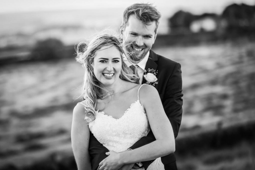 bride and groom laughing on top of a windy moorland