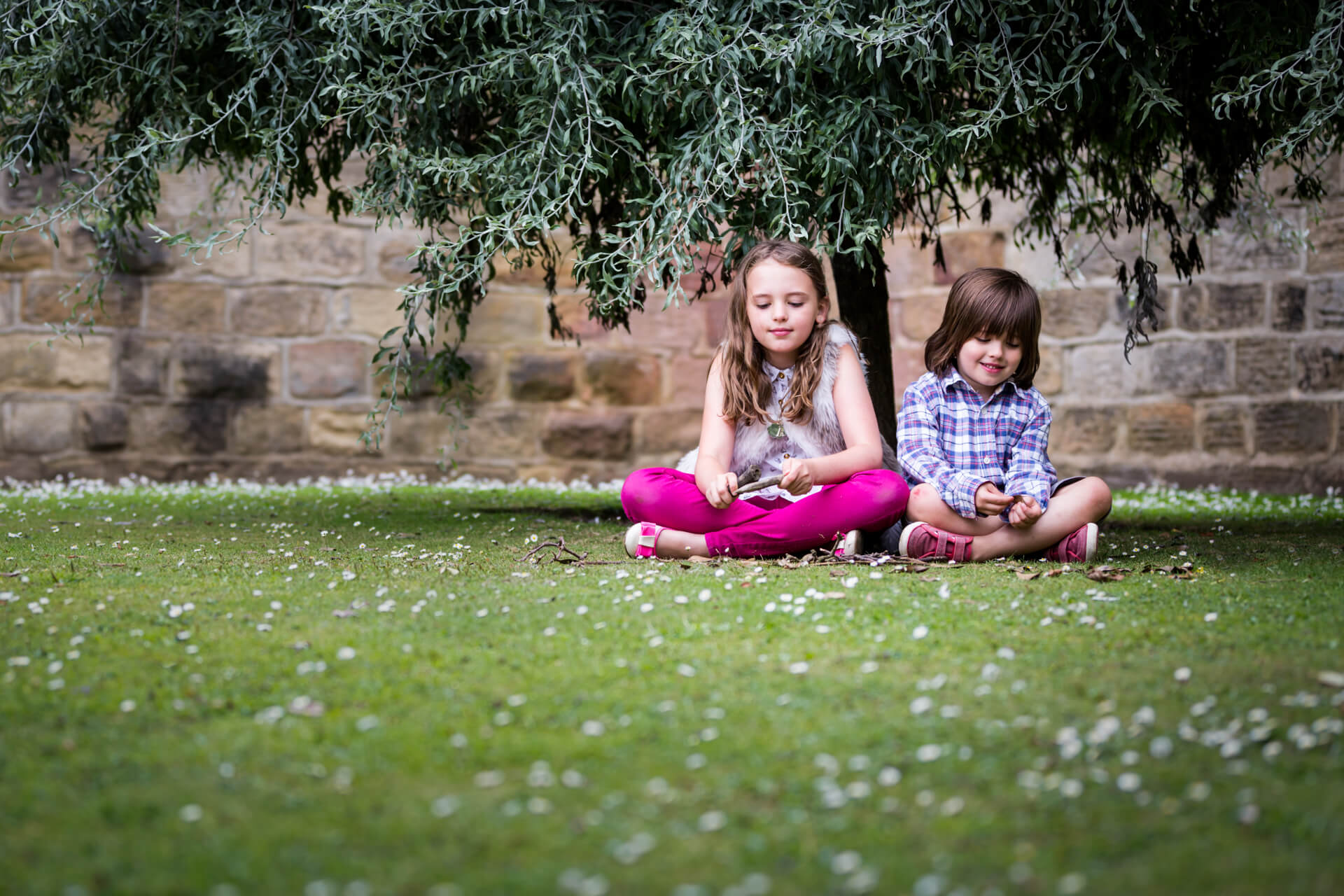 brother and sister sitting together under a tree