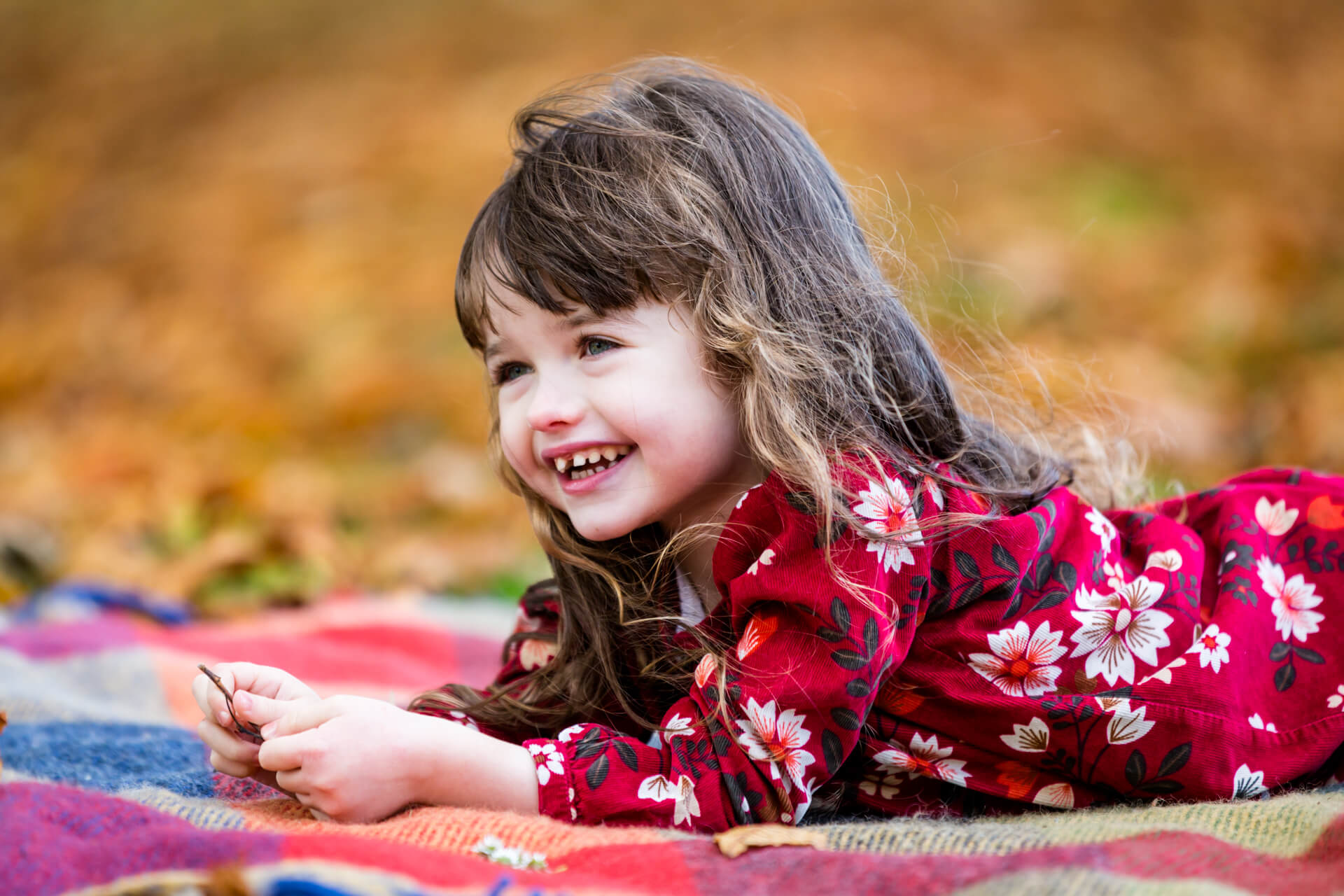 little girl lying on a rug laughing - yorkshire portrait photographer