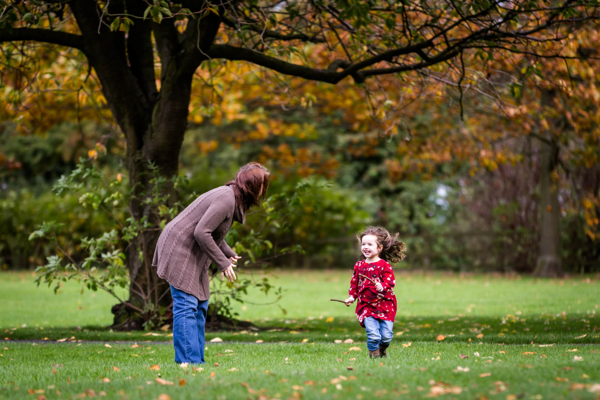 toddler running in the park with her Mum