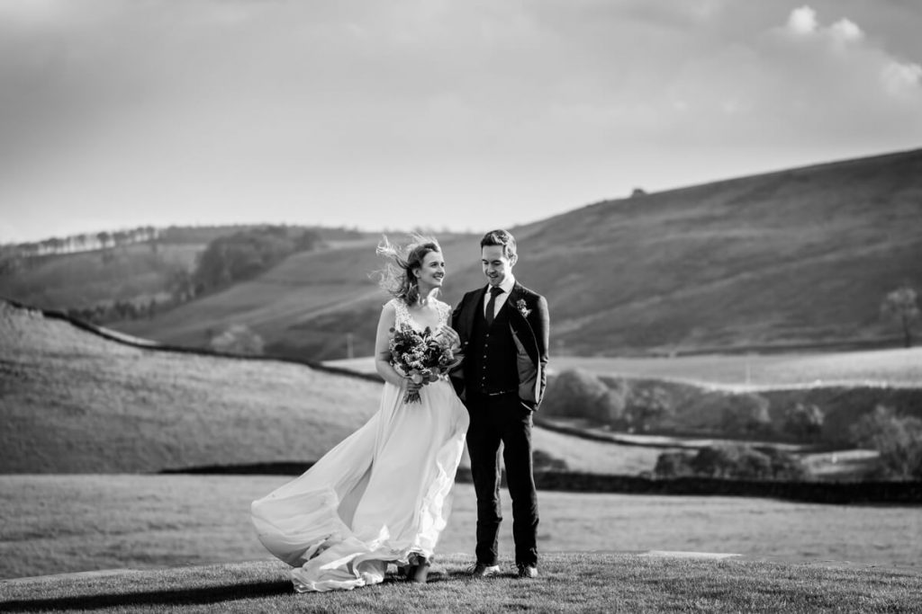 wedding couple standing in front of a stunning yorkshire dales view