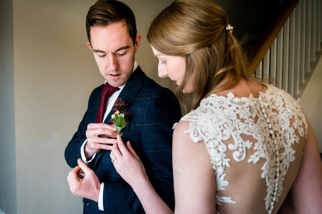 bride helps the groom to fix his buttonhole
