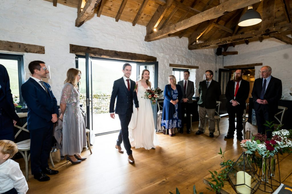 bride and groom walk into the ceremony room at telfit farm