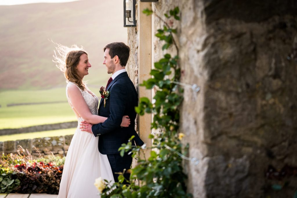bride and groom embrace in front of a dramatic view