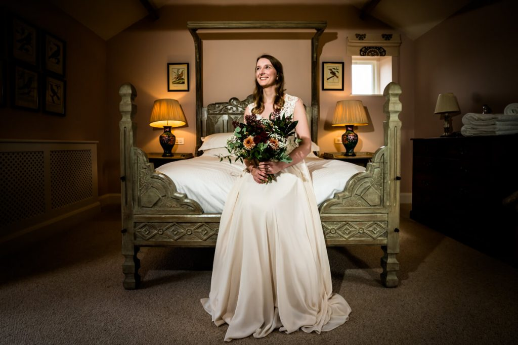 bride stirring on the edge of the bed in the bridal suite