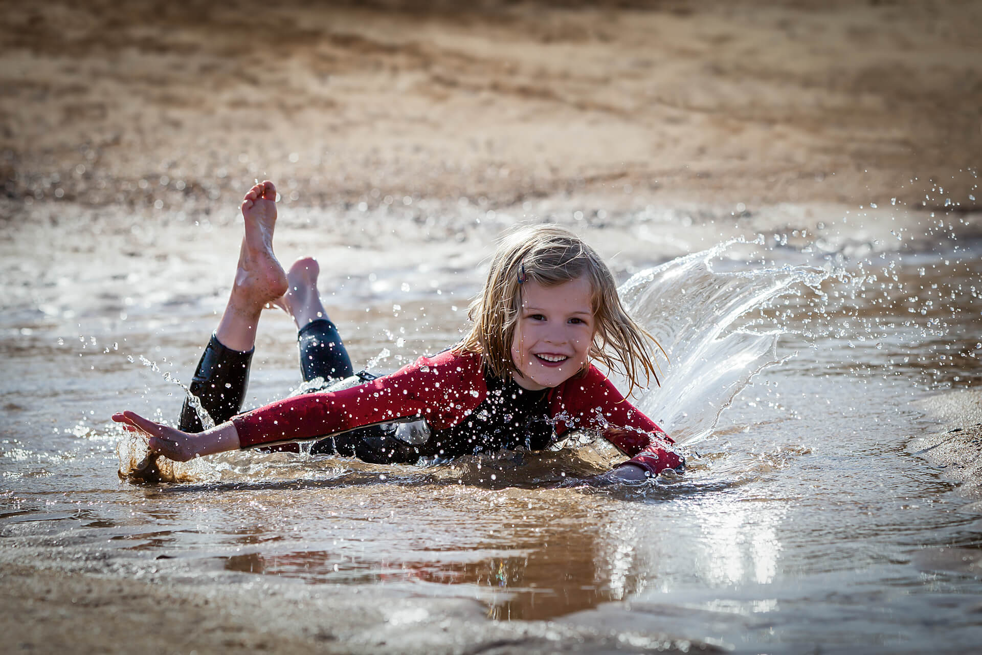 young girl splashing in a puddle