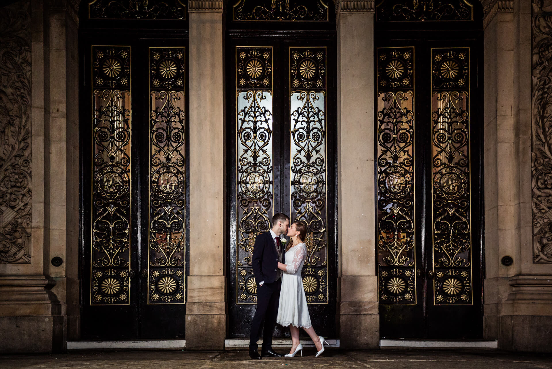 bride and groom kissing outside the leeds town hall
