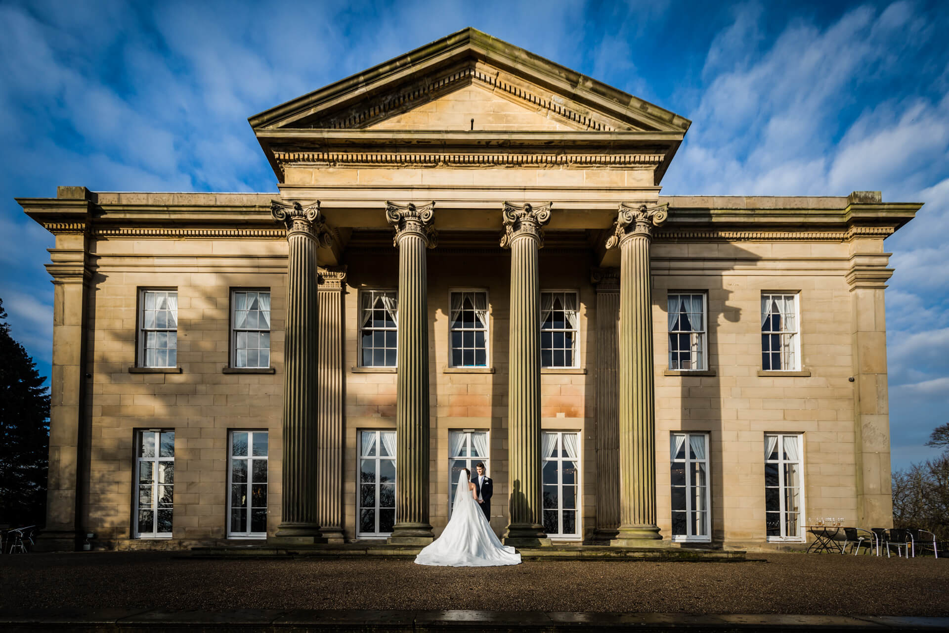 the bride and groom in front of The Mansion wedding venue in Leeds