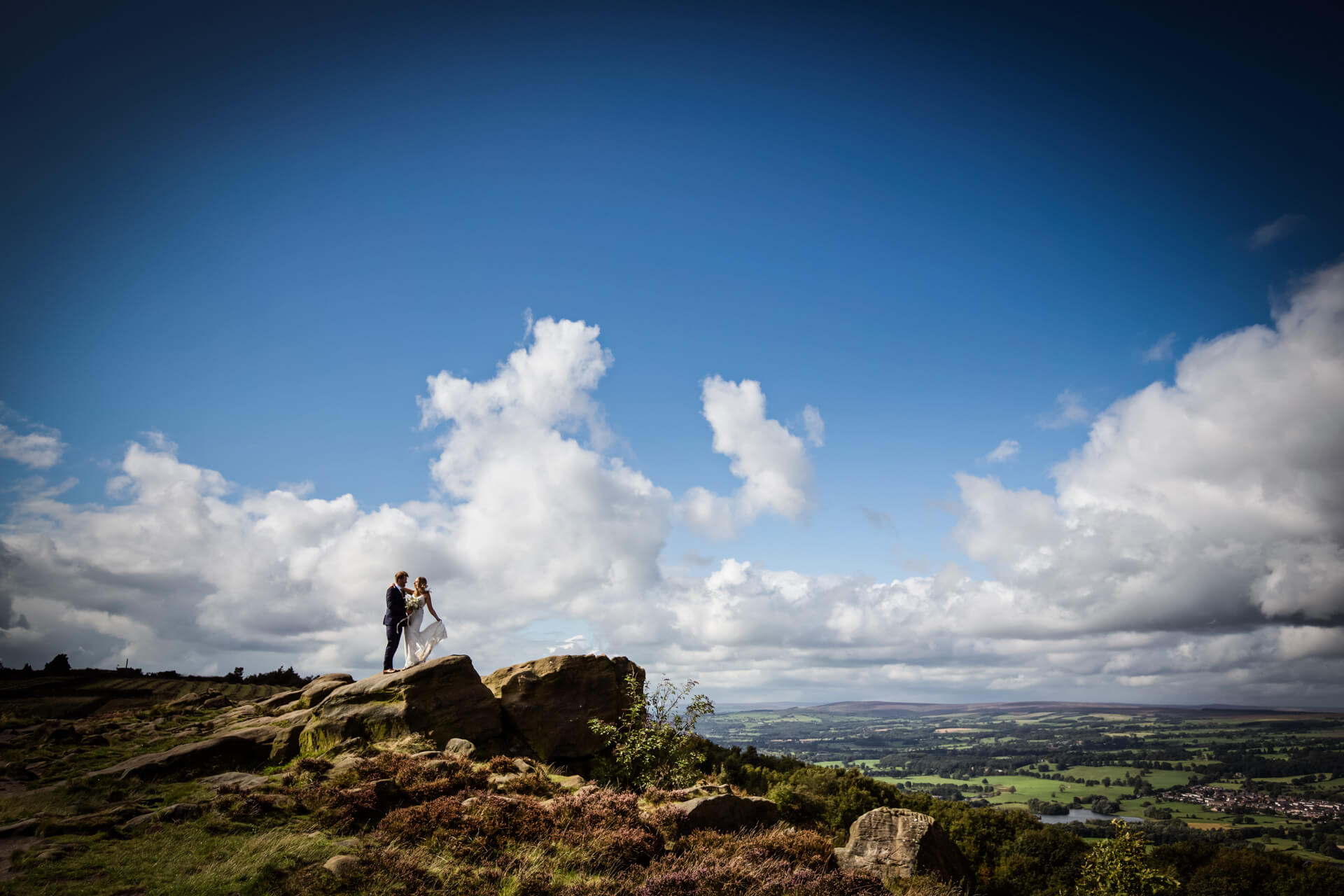 bride and groom hugging on top of a cliff overlooking a view
