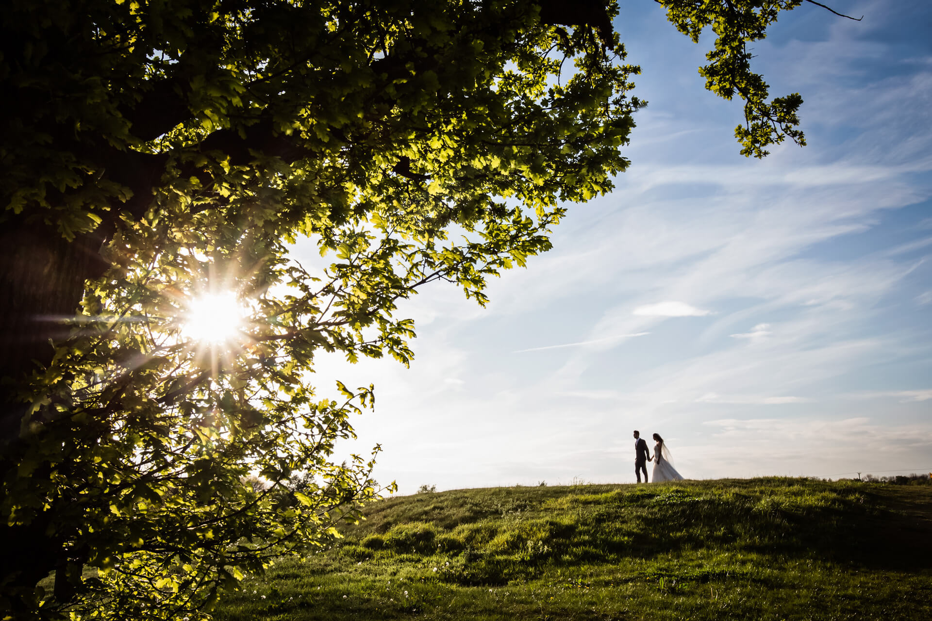 bride and groom walking hand in hand along the top of a hill