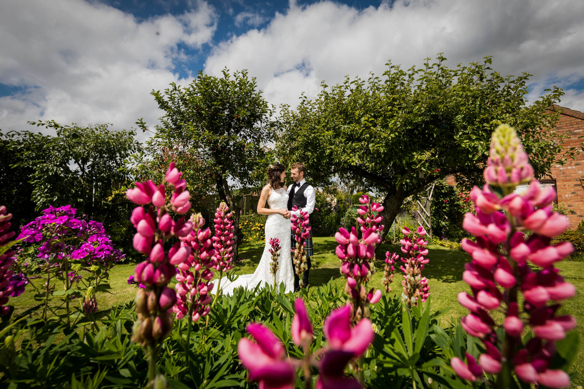 couple standing together in front of some pink flowers in a york garden