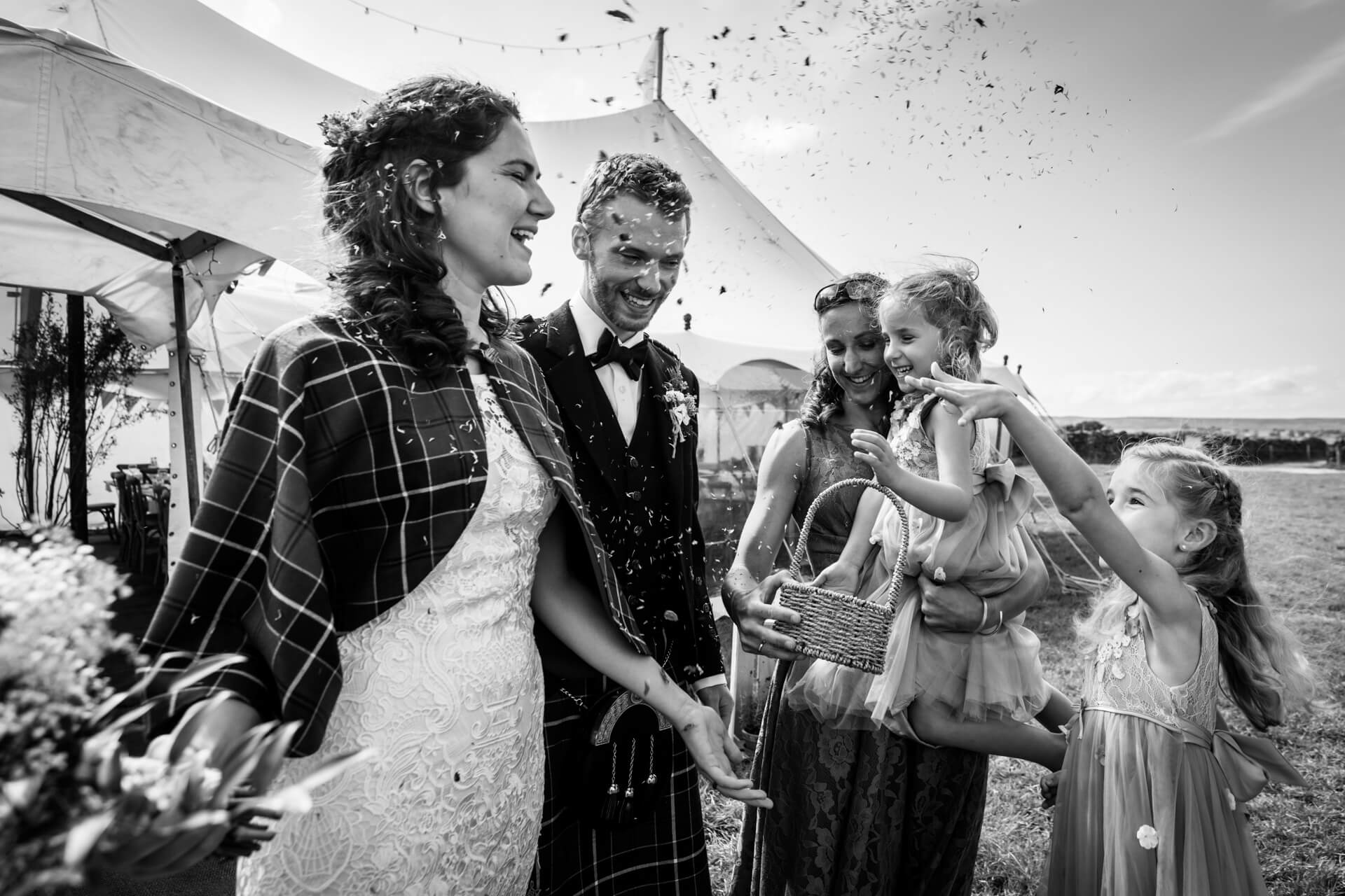two flower girls showering the couple with confetti