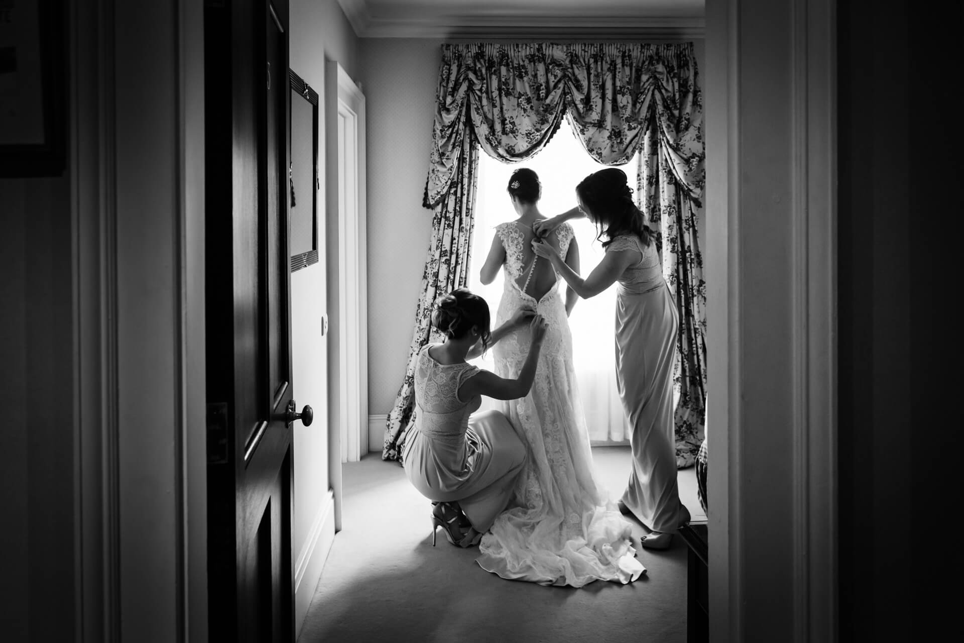 bridesmaids fixing the brides dress at the Grange hotel in york