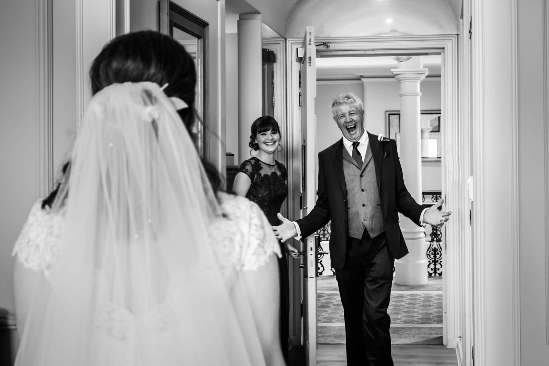 father of the bride is raising his hands with delight as he sees the bride