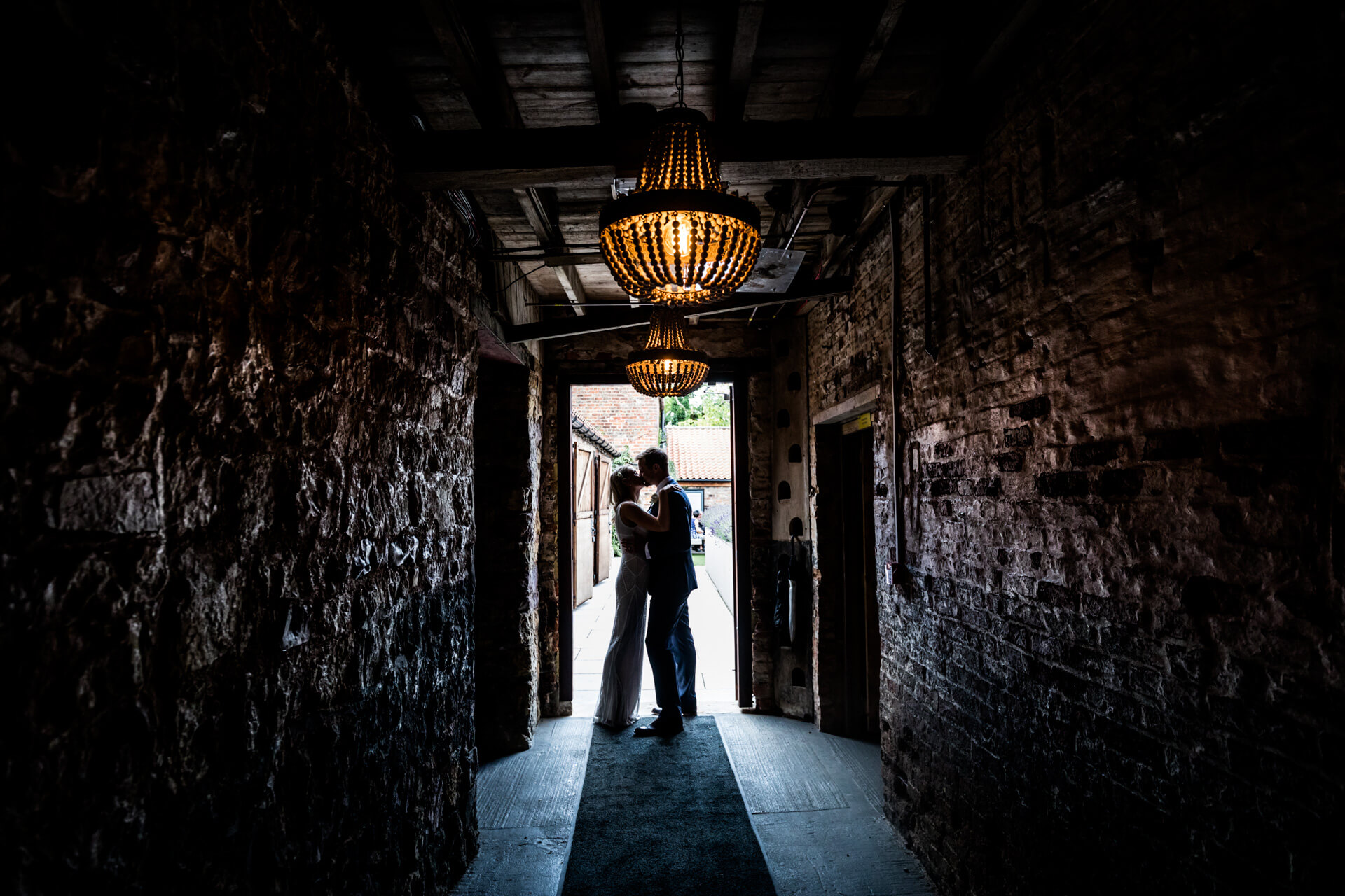 bride and groom kissing in the doorway of the normans wedding venue
