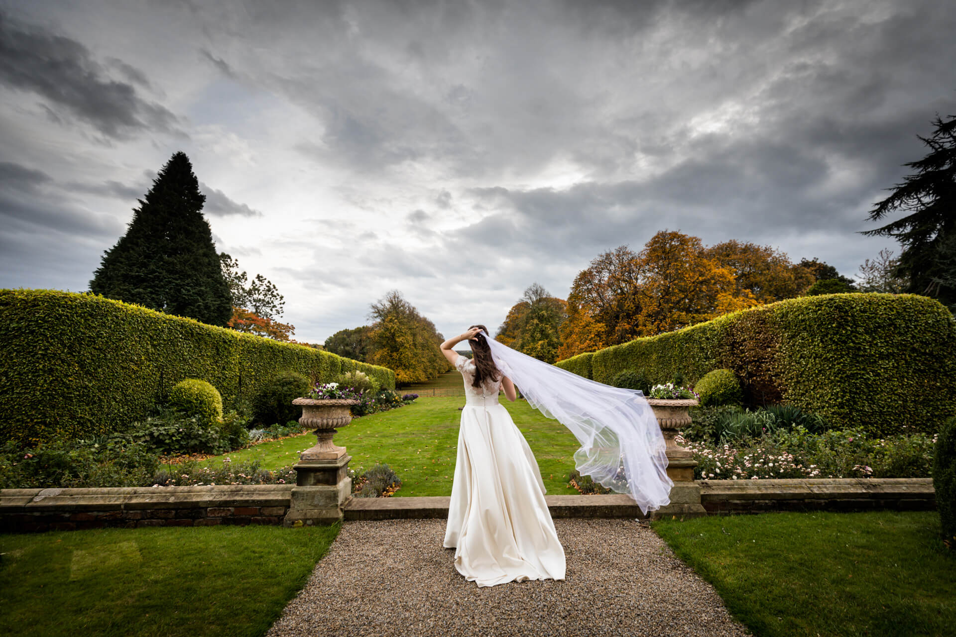 bride fixing her veil as it blows in the wind