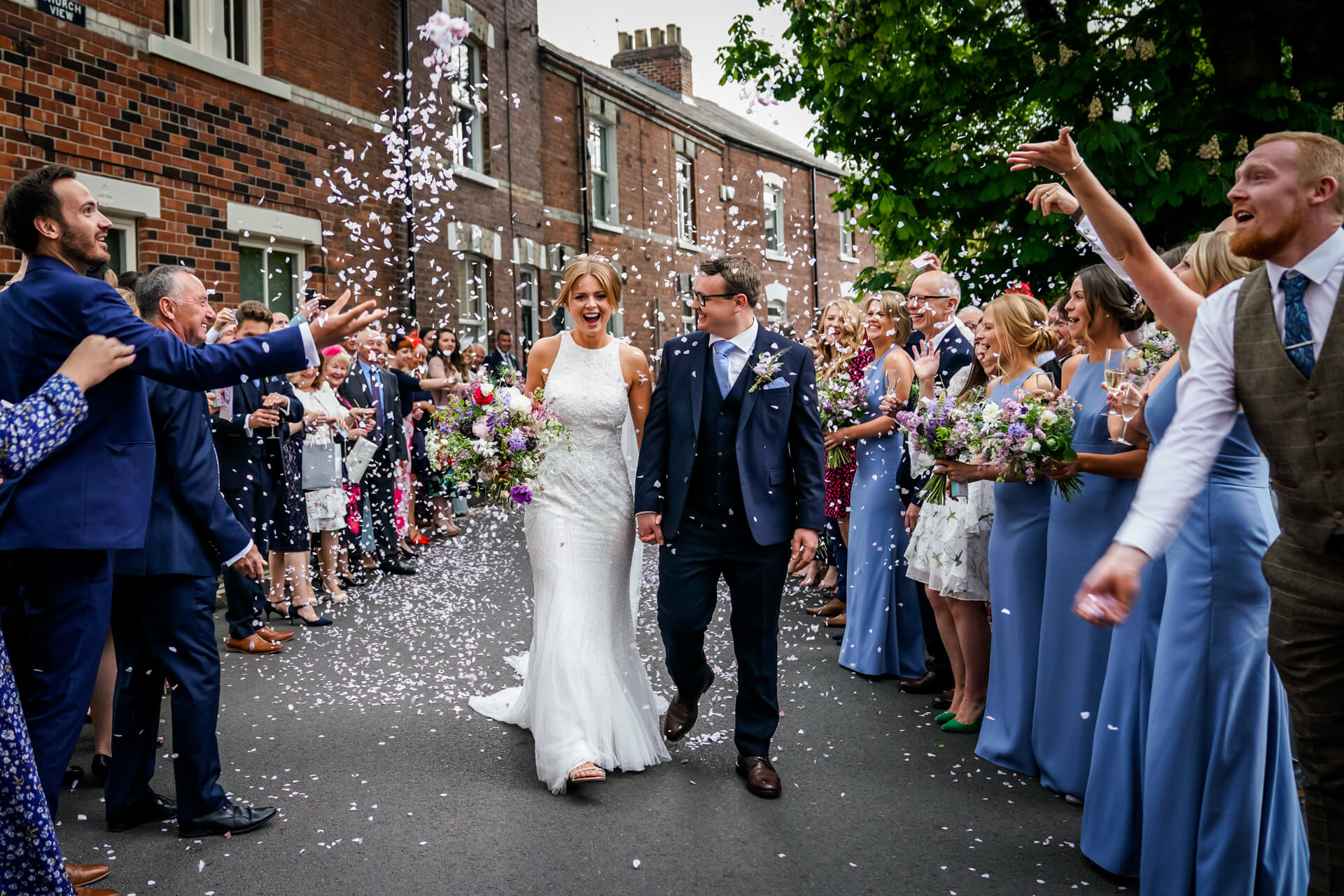 bride and groom laughing as the walk through a confetti line in york