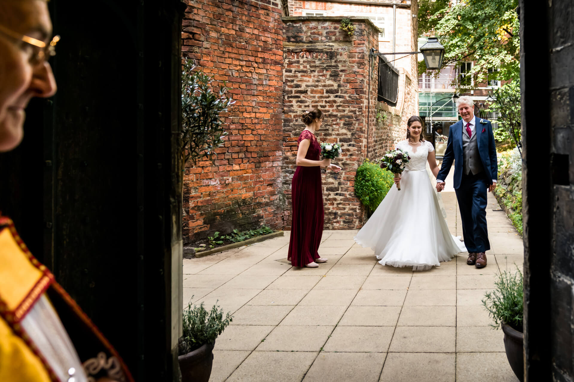 bride and her father walk into a york church whilst the priest waits for them