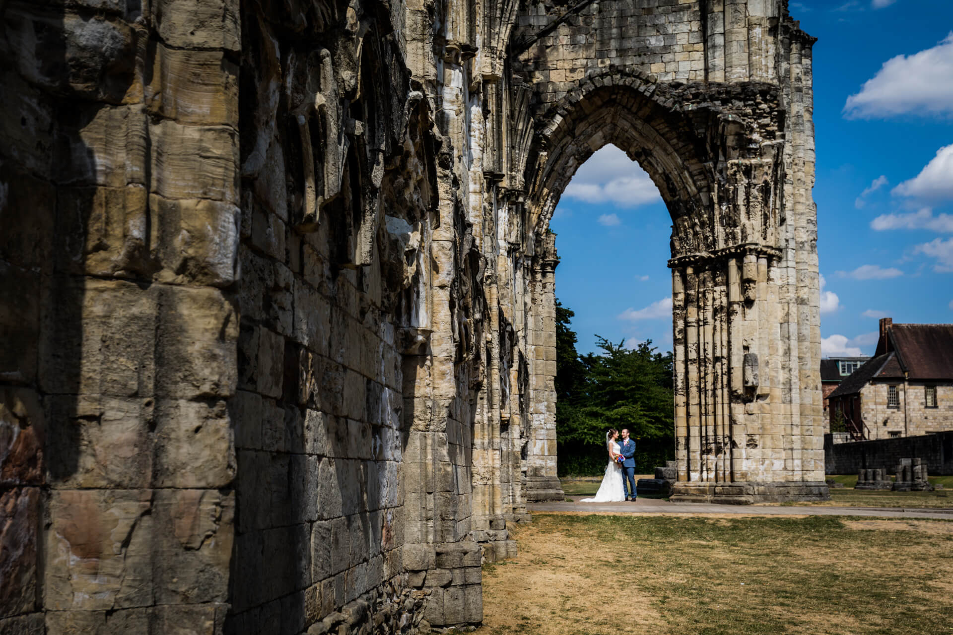 bride and groom hold hands in the archway of some run-ins in the York museum gardens