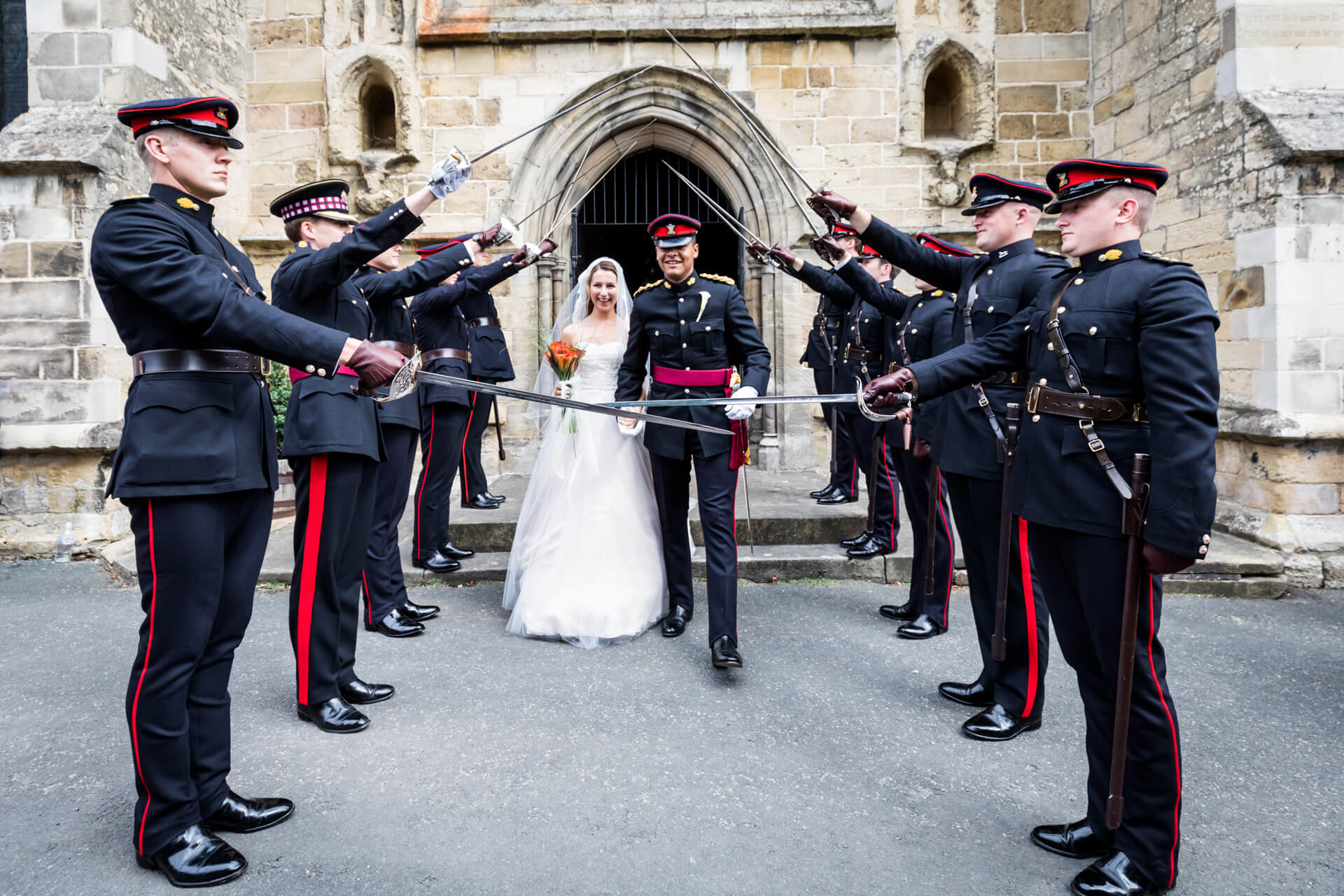 bride and groom leave the church under an arch of sabers